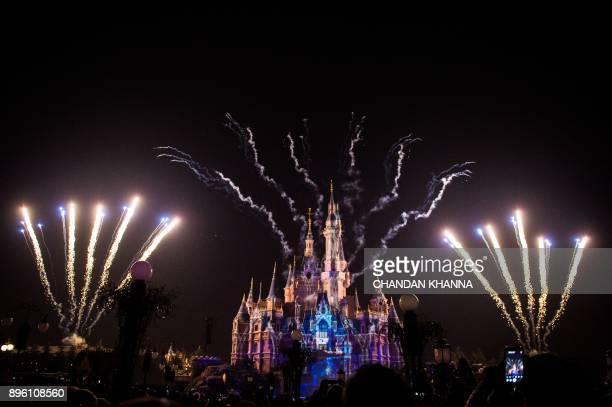 Visitors watch fireworks exploding over the Disney castle at Shanghai Disneyland in Shanghai on December 20 2017 / AFP PHOTO / CHANDAN KHANNA