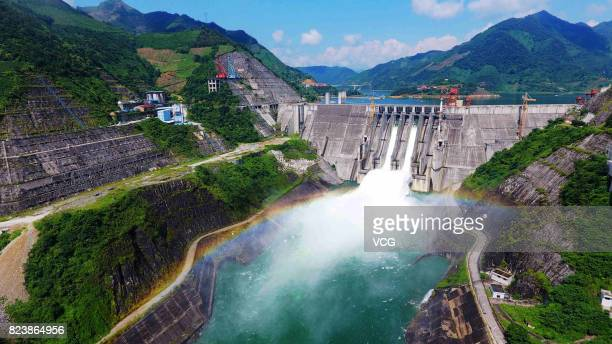 Visitors watch floodwater gushing out of Longtan Dam on July 26 2017 in Hechi Guangxi Zhuang Autonomous Region of China The Longtan hydropower...