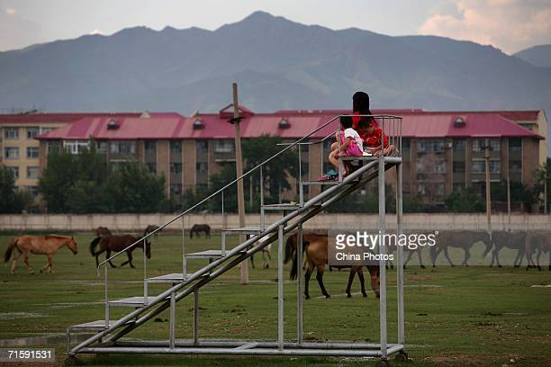 Visitors watch horses pasture at the Inner Mongolia Racetrack on August 2, 2006 in Hohhot of Inner Mongolia Autonomous Region, China. The Inner...