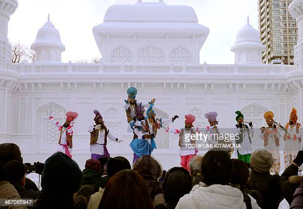 """Visitors watch Indian dancers performing a Bhangra dance at the stage in front of the large snow sculpture of """"Tomb of Itmad-ud-Daula"""" of India..."""