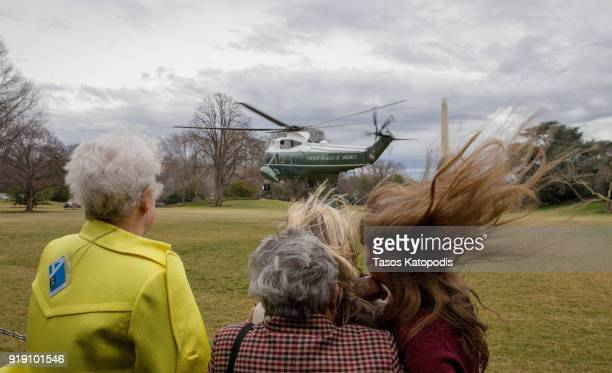 Visitors watch Marine One helicopter depart from the South Lawn of the White House on February 16 2018 in Washington DC The Trumps travel to Mar a...