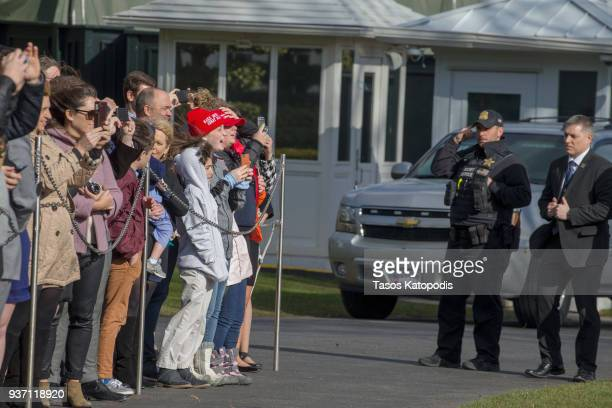 Visitors watch Marine One helicopter depart from the South Lawn of the White House on March 23 2018 in Washington DC