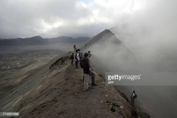 Visitors watch Tengger tribe devotees belonging to Indonesia's Hindu minority as they gather at the crater rim of Mount Bromo an active volcano in...
