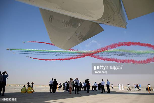 Visitors watch the Al Fursan aerobatic team perform an aerial display on the second day of the 14th Dubai Air Show at Dubai World Central in Dubai...