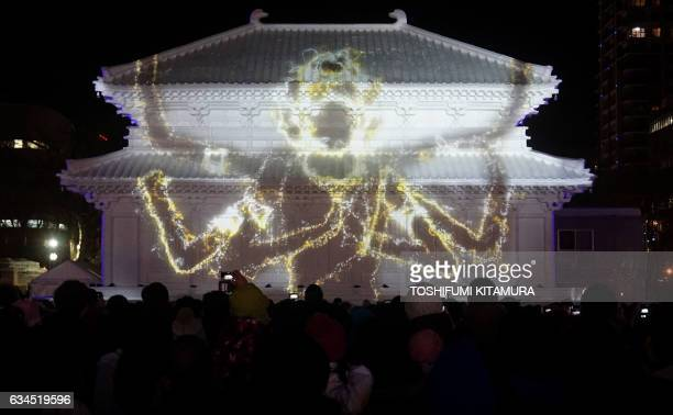 Visitors watch the projection mapping show at the snow statue of the Central Golden Hall Kofukuji temple in Nara during the Sapporo Snow Festival in...