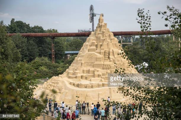 Visitors watch the Sandburg sandcastle on September 1 2017 in Duisburg Germany A local travel agency commissioned the building of the sandcastle and...