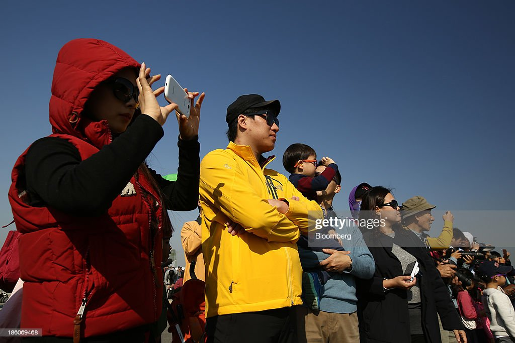 Visitors watch the South Korean Air Force Black Eagle aerobatics team, unseen, as they perform maneuvers during the Cheongju International Airport Air Show on the sidelines of the Seoul International Aerospace & Defense Exhibition 2013 at Cheongju International Airport in Cheongju, South Korea, on Friday, Oct. 25, 2013. The exhibition will run till Nov. 3. Photographer: SeongJoon Cho/Bloomberg via Getty Images