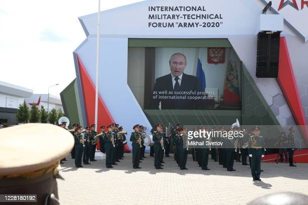 Visitors watch the speech of Russian President Vladimir Putin on the giant TV screen during the opening ceremony of the International Military...