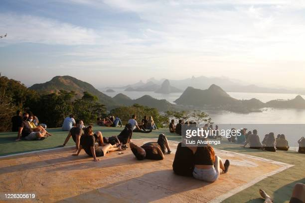 Visitors watch the sunset at Niteroi City Park amidst the coronavirus pandemic on July 11, 2020 in Niteroi, Brazil. After 3 months closed, Niteroi...