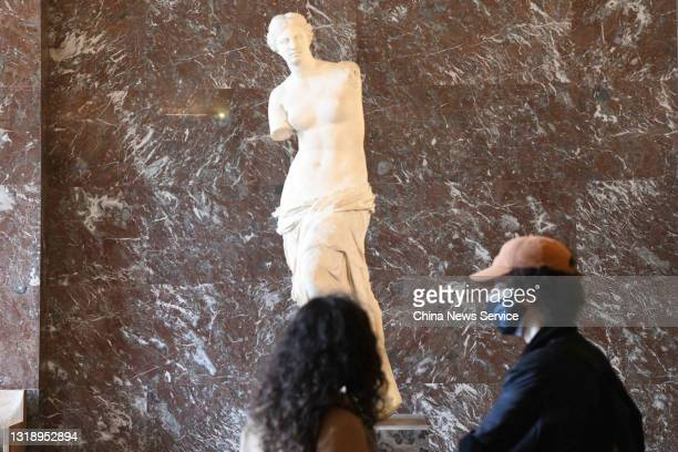 Visitors watch the Venus de Milo at the Louvre Museum on its reopening day on May 19, 2021 in Paris, France. Louvre Museum reopened to the public on...
