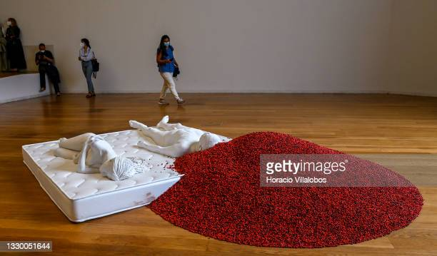 """Visitors watch """"Two Figures"""" by Chinese artist and dissident activist Ai Weiwei during a press visit to Ai Weiwei exhibition """"Entrelaçar: Pequi..."""
