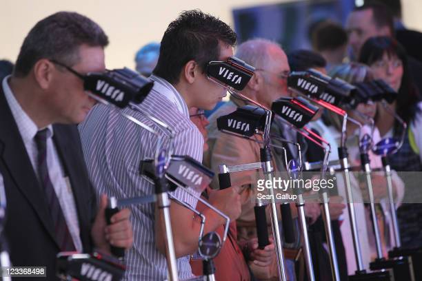 Visitors wear 3D glasses while watching 3D camcorder presentations at the Panasonic stand at the IFA 2011 consumer electonics and appliances trade...