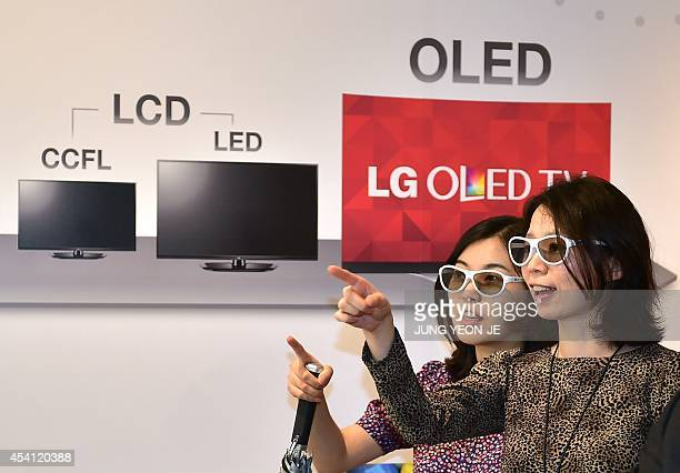 Visitors wear 3D glasses while watching LG's Ultra OLED TV during its unveiling ceremony in Seoul on August 25 2014 LG Electronics announced the...