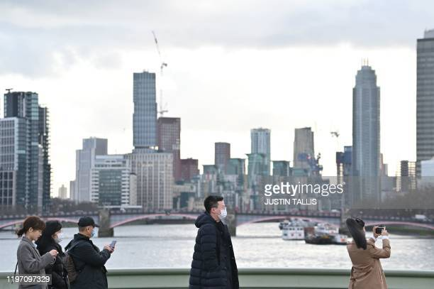 Visitors wear face masks as they take photographs near the Thames embankment in central London on January 28 2020 Around 1500 people who came to...