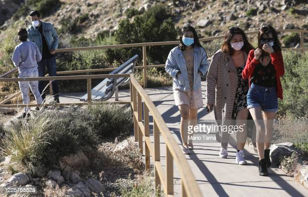 Visitors wear face masks on a walking path in Joshua Tree National Park one day after the park reopened after being closed for two months due to the...