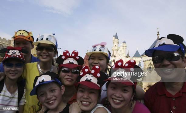 Visitors wear hats showing Disney characters at Hong Kong Disneyland September 12 2005 in Hong Kong
