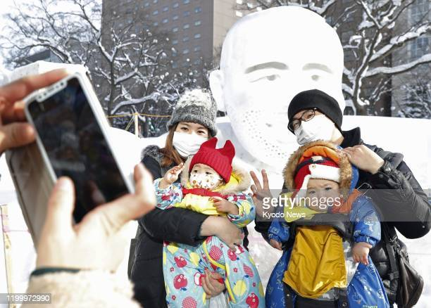 Visitors wear masks at the annual Sapporo Snow Festival in Hokkaido, northern Japan, on Feb. 11 amid concern over the spread of a new coronavirus.