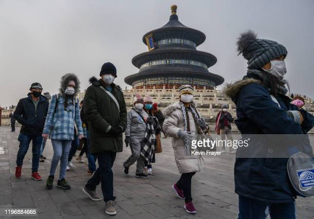Visitors wear protective masks as they tour the grounds of the Temple of Heaven which remained open during the Chinese New Year and Spring Festival...