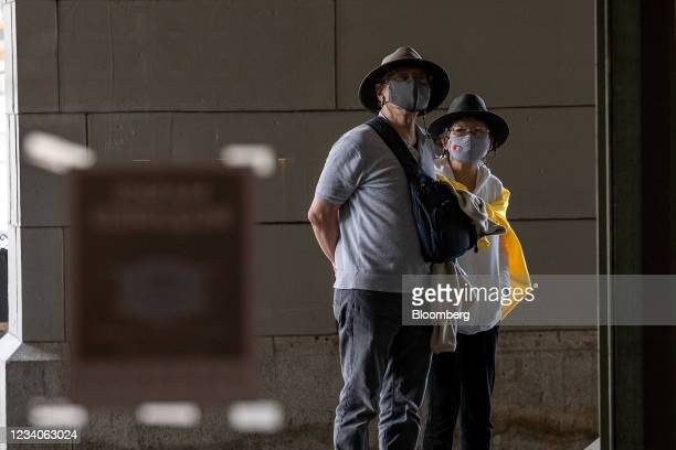 Visitors wear protective masks outside of the Ferry Building in San Francisco, California, U.S., on Monday, July 19, 2021. Officials in the San...