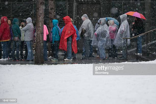 Visitors wear rain ponchos and hold umbrellas as they wait to enter the Capitol Visitor Center in Washington DC US on Monday March 25 2013 An early...