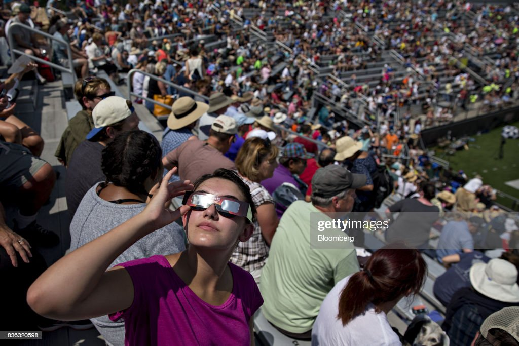 Visitors wear solar viewing glasses while looking at the sun during an eclipse viewing event on the campus of Southern Illinois University (SIU) in Carbondale, Illinois, U.S., on Monday, Aug. 21, 2017. Millions of Americans across a 70-mile-wide (113-kilometer) corridor from Oregon to South Carolina will see the sky darken as the sun disappears from view total during the eclipse, with Carbondale seeing totality for 2 minutes and 38 seconds. Photographer: Daniel Acker/Bloomberg via Getty Images
