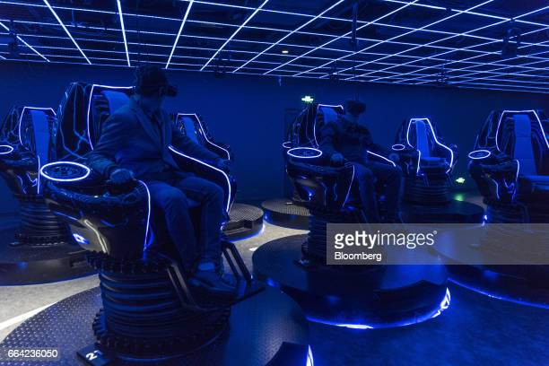 Visitors wear virtual reality headsets while participating in a demonstration in a 4D cinema that can accommodate 23 people at the SoReal virtual...