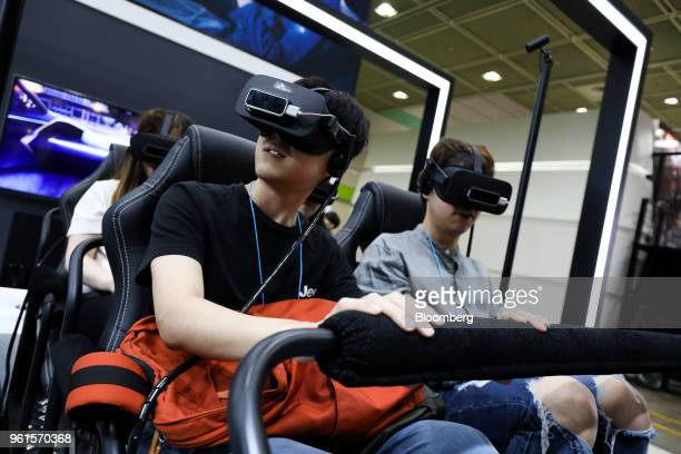Visitors wear virtual reality headsets while playing a video game at the SK Telecom Co booth during the World IT Show 2018 in Seoul South Korea on...