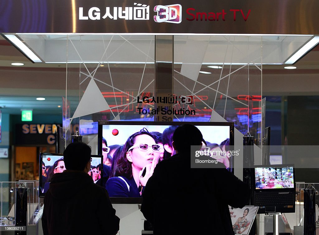Visitors wearing 3-D glasses look at a LG Electronics Inc. 3-D smart television at the company's showroom in the COEX mall in Seoul, South Korea, on Wednesday, Feb. 1, 2012. LG Electronics Inc., South Korea's second-largest electronics maker, posted the first profit at its handset business in seven quarters, helping shares reverse earlier losses in Seoul trading. Photographer: SeongJoon Cho/Bloomberg via Getty Images
