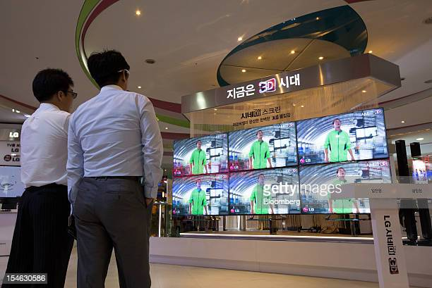 Visitors wearing 3D glasses look at LG Electronics Inc Cinema 3D televisions at the company's showroom in the COEX mall in Seoul South Korea on...