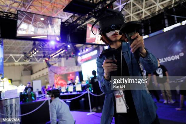 Visitors wearing a VR headset play a video game in the Wargaming booth during the Tokyo Game Show 2017 at Makuhari Messe on September 21, 2017 in...
