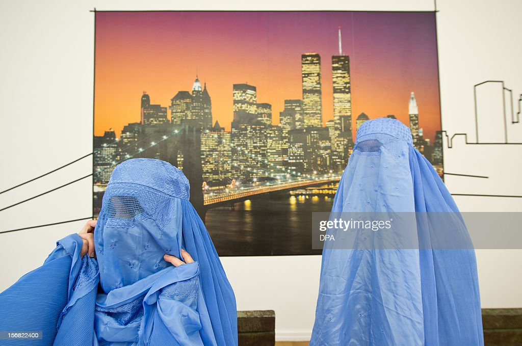 Visitors wearing burkas, walk in front of a photograph of the German artist Naneci Yurdaguel, which shows the skyline of New York and the World Trade Center on November 22, 2012 during the exhibition 'Burquoi' in Wiesbaden, southwestern Germany. One focus of Yurdaguel's artistic engagement is topics on national and religious identity, migration, social exclusion, cultural appropriation and mistrust. They are constantly picked up and are treated critically, often in relation to current public debates, to intervene in social discourse.