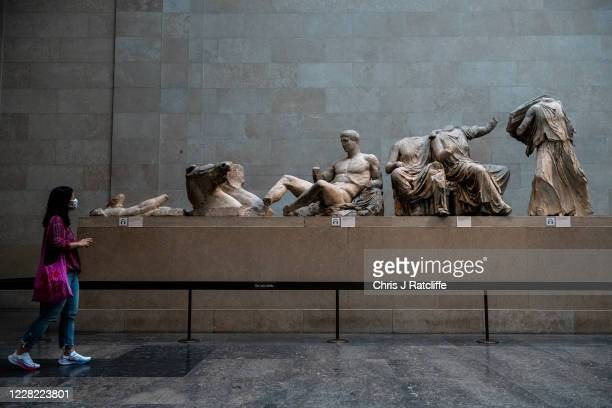 Visitors wearing face masks look at sculptures in the Parthenon gallery at the British Museum on August 27, 2020 in London, England. The British...
