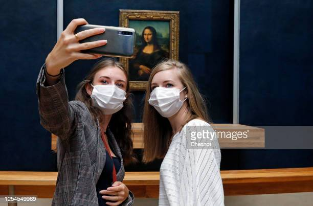 """Visitors wearing face masks take a selfie with the painting of """"Mona Lisa"""" also known as by Italian artist Leonardo Da Vinci at the Louvre museum on..."""
