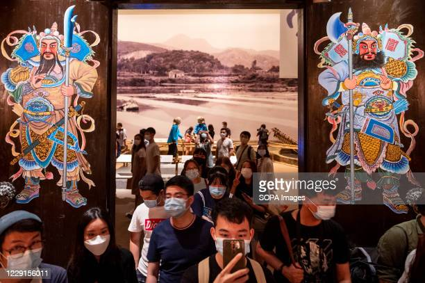 Visitors wearing face masks take pictures of lanterns at the exhibition at the Hong Kong museum of History. The permanent exhibition of the museum...