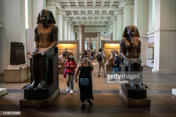 Visitors wearing face masks walk through the Egyptian exhibit at the British Museum on August 27, 2020 in London, England. The British Museum has...