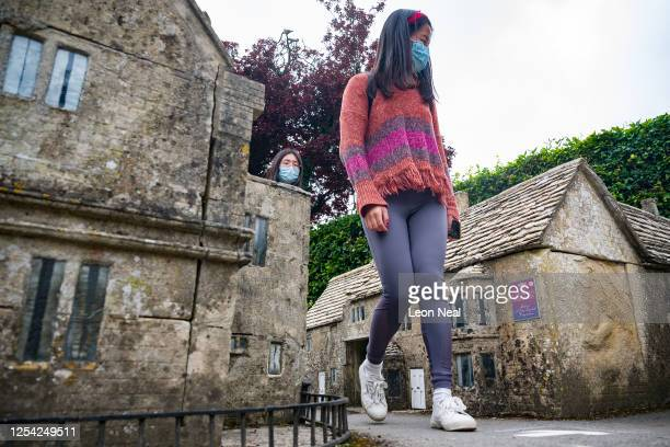 Visitors wearing face masks walk through the miniature streets of the Model Village on July 04 2020 in BourtonontheWater England Model villages are...