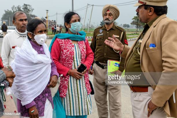 Visitors wearing facemasks interact with police personnel that turn them away at the entrance of IndiaPakistan Wagah Border post about 35 kms from...
