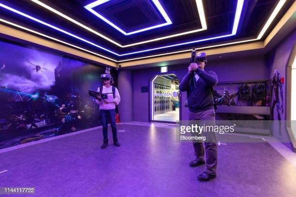 Visitors wearing HTC Corp Vive virtual reality headsets play a video game at the KT Corp VRIGHT VR game zone in Seoul South Korea on Tuesday Jan 29...