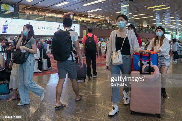 Visitors wearing masks arrive at the departure hall of Changi Airport on January 25, 2020 in Singapore. Yesterday Singapore confirmed its third case...