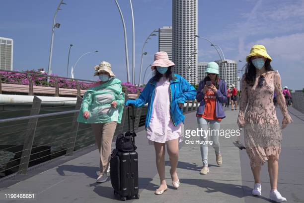 Visitors wearing masks walk through the Merlion Park on January 26 2020 in Singapore Singapore has confirmed four cases of the deadly coronavirus...