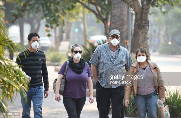 Visitors wearing masks walk to protect themselves from smoke and ash from the Thomas Fire walk on State Street the main shopping street in Santa...