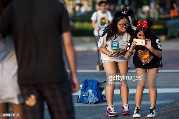 Visitors wearing Mickey Mouse and Minnie Mouse ears take a photograph using an Apple Inc iPhone at Walt Disney Co's Disneyland Resort in Hong Kong...