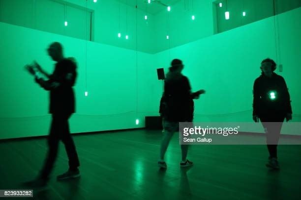 Visitors wearing milky goggles and devices strapped to their bodies that emit light in different colors and have haptic engines walk through the...
