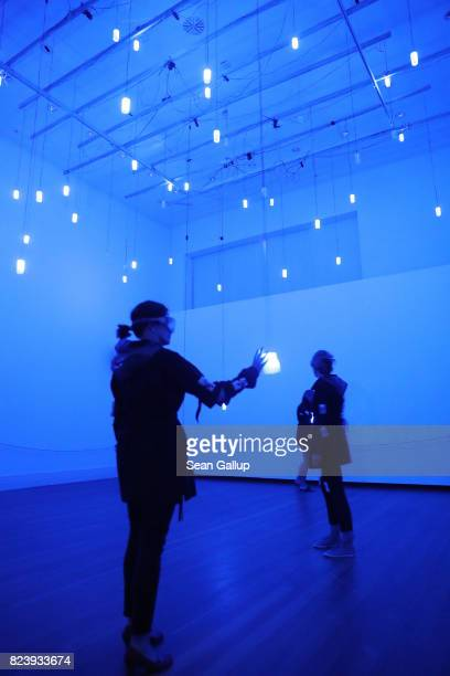 Visitors wearing milky goggles and devices strapped to their bodies that emit light in different colors and have haptic engines hold hands as they...