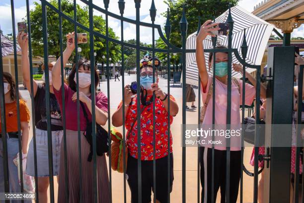 Visitors wearing protective face masks take photographs behind a fence at Walt Disney Co's Disneyland Resort on June 18 2020 in Hong Kong China