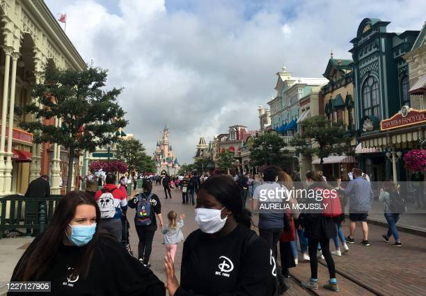 Visitors wearing protective face masks, walk down the Main Street of Disneyland Paris in Marne-la-Vallee, near Paris, on July 15 as Disneyland Paris...