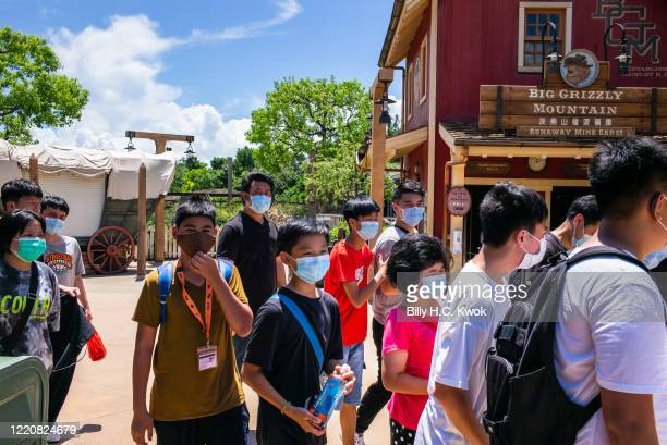 Visitors wearing protective face masks walk in Walt Disney Co's Disneyland Resort on June 18 2020 in Hong Kong China