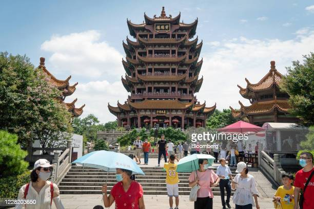 Visitors wearing protective mask walk in the grounds of the Yellow Crane Tower in Wuhan China on Saturday Aug 8 2020 More than eight months after...