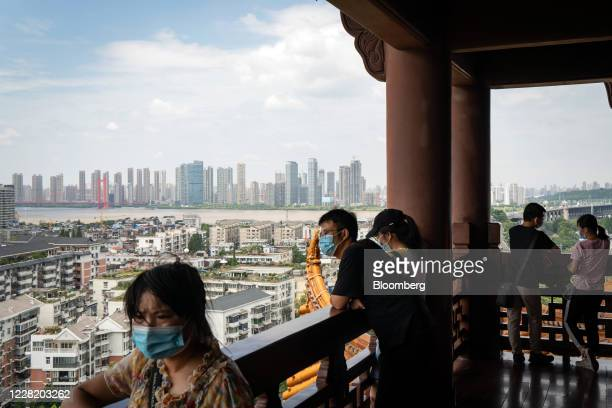 Visitors wearing protective masks take in the view from the Yellow Crane Tower in Wuhan, China, on Saturday, Aug. 8, 2020. More than eight months...