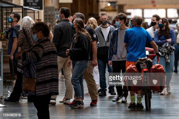 Visitors wearing protective masks walk inside the Ferry Building in San Francisco, California, U.S., on Monday, July 19, 2021. Officials in the San...